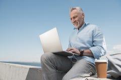 Popielaty z włosami mężczyzna pisać na maszynie na laptopie podczas gdy siedzący przy quay Fotografia Royalty Free