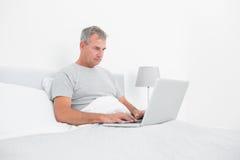 Popielaty z włosami mężczyzna używa laptop w łóżku Fotografia Stock