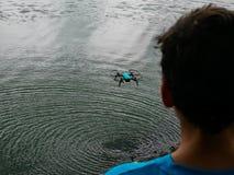 Popiera chłopiec lata błękitnego trutnia nad jeziorem tworzy pluskoczącego powierzchnia zamazującego przedpole fotografia royalty free