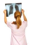 Popiera lekarka egzamininuje Xray wizerunek Fotografia Royalty Free