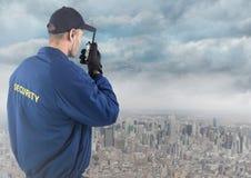 Popiera pracownik ochrony z walkie talkie przeciw linii horyzontu i chmurom Fotografia Royalty Free
