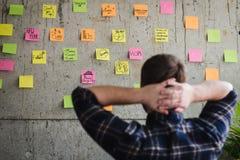 Popiera przedsiębiorcy obsiadanie w biurze i patrzeje kolorowy stic zdjęcia stock