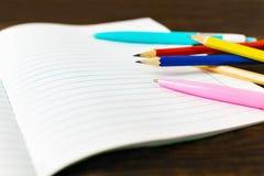 Popiera szkoła i edukacji pojęcie - pusty nutowy papier z piórami i ołówkami na drewnianym tle kosmos kopii zdjęcie stock