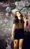 Popiera szkoła po wakacji, śliczna nastoletnia istna brunetki dziewczyna w sala lekcyjnej przy blackboard, stylu życia pojęcia lu Obrazy Royalty Free