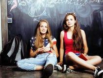 Popiera szkoła po wakacji, dwa nastoletniej istnej dziewczyny w sala lekcyjnej z blackboard malującym wpólnie, styl życia Obraz Stock