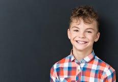 Popiera szkoły pojęcie - szczęśliwa chłopiec patrzeje kamerę obraz royalty free