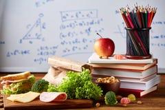 Popiera szkoły pojęcie, szkolne dostawy, ciastka i lunchbox nad białym chalkboard, selekcyjna ostrość, zakończenie Obrazy Stock