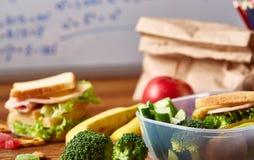 Popiera szkoły pojęcie, szkolne dostawy, ciastka, pakujący lunch i lunchbox nad białym chalkboard, selekcyjna ostrość zdjęcie royalty free