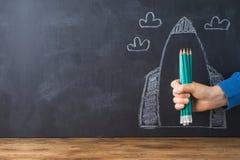 Popiera szkoły pojęcie z ręki mienia ołówkami nad chalkboard rakiety nakreślenia tłem obrazy royalty free