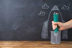Popiera szkoły pojęcie z ręki mienia ołówkami nad chalkboard rakiety nakreślenia tłem fotografia stock
