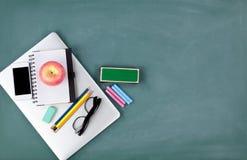 Popiera szkoły pojęcie z technologią i materiały na zielonym chalkboard tle zdjęcia stock