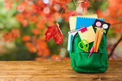 Popiera szkoły pojęcie z torba plecakiem i szkolne dostawy na drewnianym stole nad jesieni bokeh tłem zdjęcie royalty free