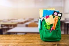 Popiera szkoły pojęcie z torba plecakiem i szkolne dostawy na drewnianym stole nad sali lekcyjnej tłem zdjęcie stock
