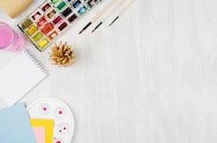 Popiera szkoły tło akwareli farby, paleta, muśnięcia, barwioni ołówki na białym drewno stole, - materiały dla twórczości - zdjęcie stock