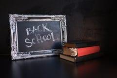 Popiera szko?a, kreda w rocznik ramie Tekst na chalkboard i sterta podr?czniki obrazy stock