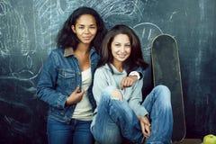Popiera szko?a po wakacji, dwa nastoletniej istnej dziewczyny w sala lekcyjnej z blackboard maluj?cym wp?lnie, styl ?ycia obrazy royalty free