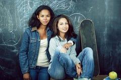 Popiera szko?a po wakacji, dwa nastoletniej istnej dziewczyny w sala lekcyjnej z blackboard maluj?cym wp?lnie, styl ?ycia obraz royalty free