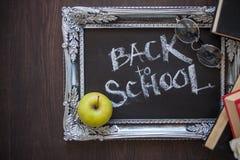 Popiera szko?a, tekst na chalkboard w rocznik ramie, i podr?czniki zdjęcia royalty free