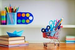 Popiera szkoły wózek na zakupy z dostawami na Drewnianym stole Zdjęcia Stock