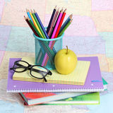 Popiera szkoły pojęcie. Jabłko, barwioni ołówki i szkła na stosie książki nad mapą, Obrazy Royalty Free