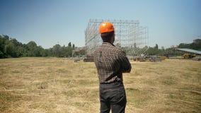 Popiera ufny architekt patrzeje budowę przyszłościowa fabryka, stoi z krzyżować rękami na słomy polu zbiory
