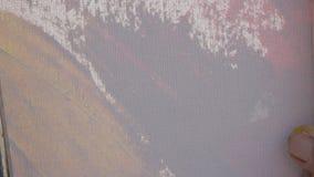 Popiera w górę widoku malującego męską artysta ręką z szeroką szpachelką i kolor farbą przy biała kanwa akrylowego lub nafcianego zbiory wideo