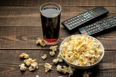 Popkorn, koka-kola i TV pilot na brązu drewnianym tle, pojęcie dopatrywanie filmy w domu zdjęcia royalty free