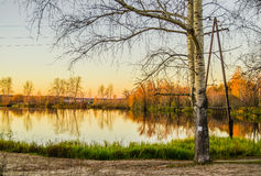 Poplar, cottonwood and birches near the pond at sunset. Autumn natural landscae with lake birch trees at sunset ion orange, blue and green colors Royalty Free Stock Photos