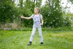 Poplar fluff. Little  girl  playing with poplar fluff on the green park outdoor Stock Photos
