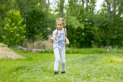 Poplar fluff. Little  girl  playing with poplar fluff on the green park outdoor Stock Photo