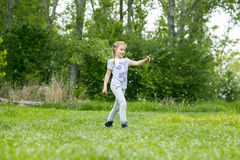Poplar fluff. Little  girl  playing with poplar fluff on the green park outdoor Royalty Free Stock Images
