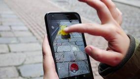 Pople que juega Pokemon VA el teléfono elegante aumentado golpe app de la realidad almacen de video