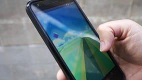 Pople que juega Pokemon VA el teléfono elegante aumentado golpe app de la realidad metrajes