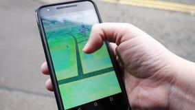 Pople que juega Pokemon VA el teléfono elegante aumentado golpe app de la realidad almacen de metraje de vídeo