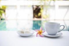 Popołudniowej herbaty czas przy basen stroną, biała herbaciana filiżanka z tajlandzkim cukierki na bielu stole nad zamazanym pływ zdjęcie stock