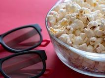 Poporn in der Schüssel mit Gläsern ein 3d auf Rot Stockbild