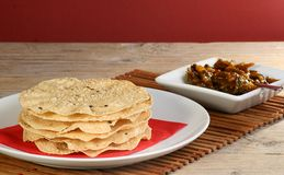 Poppadums and pickle. Poppadoms stacked on a plate with a dish of green chilli pickle Royalty Free Stock Photos