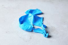 Popped blue latex balloon. On grey background royalty free stock images