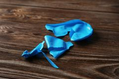 Popped blue latex balloon. On wooden background royalty free stock images