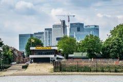 Poppelroddklubba framme av de kommersiella byggnaderna av Canary Wharf Arkivfoto