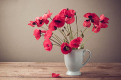 Poppies in cup on wooden table Royalty Free Stock Photo