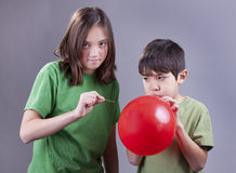 Popping brother's ballooon. Stock Photos