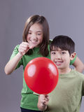 Popping her brother's balloon. Older sister going to pop her little brother's balloon royalty free stock image