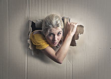 Popping out. A blonde woman is popping out from a white cardboard Royalty Free Stock Photography