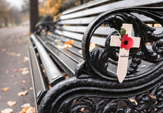 Poppy appeal remembrance cross on cast iron bench Rememberance. Empty bench with Poppy appeal remembrance cross with fallen leaves Rememberance Day Stock Images