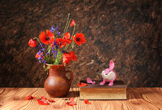 Poppy in a ceramic vase and plastic toy Royalty Free Stock Photo