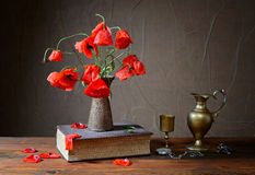 Poppy in ceramic vases, books and metal carafe Stock Photo