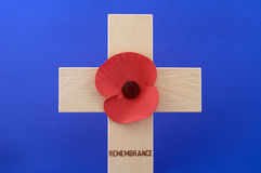 Poppy on Cross. Remembrance Day Poppy on wooden cross against blue background Stock Image