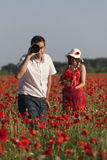 Poppy fun. A photographer and a young women harvesting poppy in a poppy field Royalty Free Stock Image