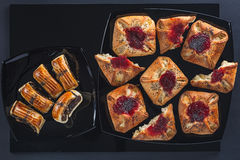 Poppy and jam cakes of a different form on small and big square ceramic plates. Poppy and jam cakes of a different form on small and big black square ceramic stock images